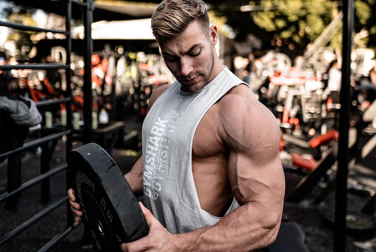 Bodybuilder Looking at Biceps while Holding Weight