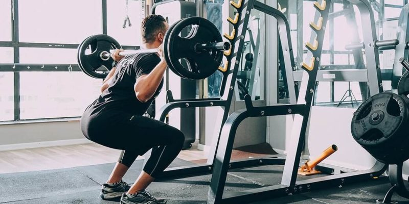 Man Doing Squats at a Gym