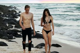 Shirtless Man with a Good Physique Walking Next To a Woman on a Beach