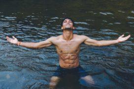 Shirtless Man Flexing in Lake