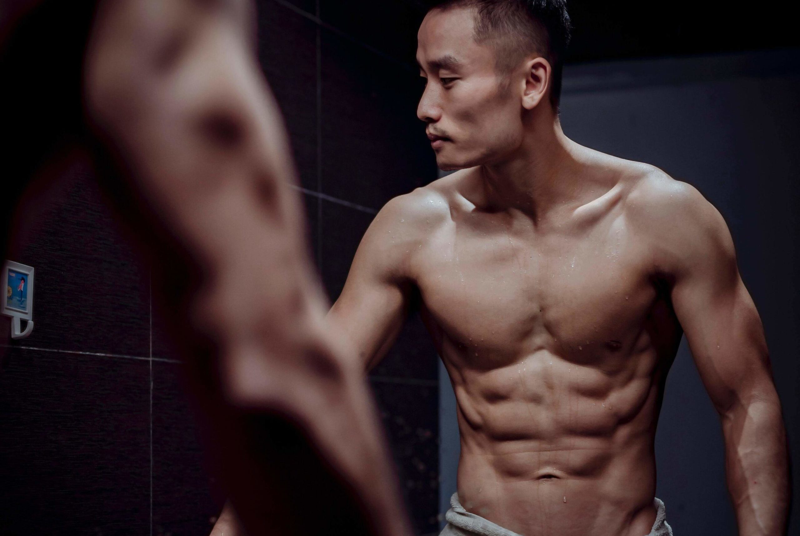Shirtless Man Doing the Stomach Vacuum Exercise in Bathroom