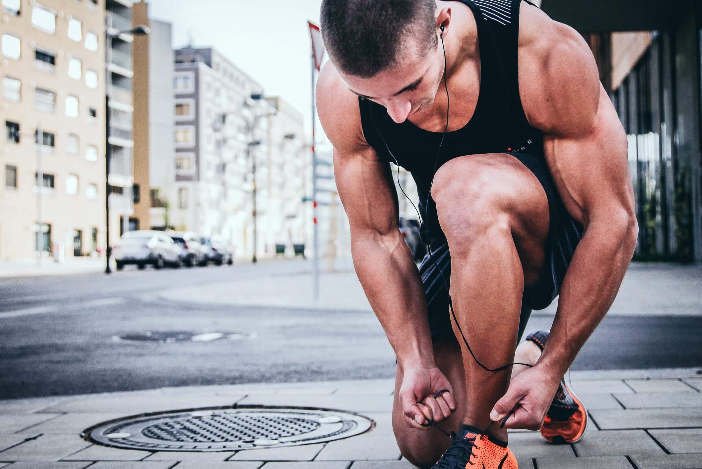 Muscular Man Tying Shoe on Sidewalk