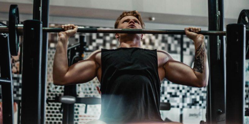 Bodybuilder Doing Barbell Shoulder Press at a Gym
