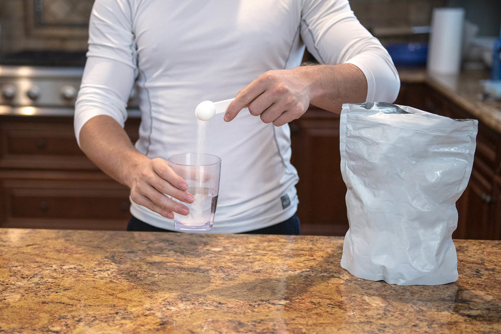 Man Pouring Beta-Alanine into a Cup